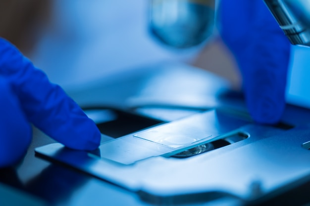 Chiuda in su del microscopio al laboratorio di sangue, concetto di scienza e tecnologia