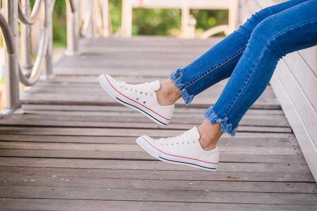 Chiuda in su del modello in scarpe da tennis bianche