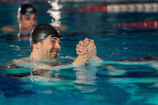 Chiuda in su del nuotatore maschio felice che agita un'altra mano dei nuotatori