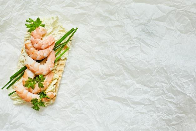 Chiuda in su del panino aperto con i gamberi, cipolle su priorità bassa bianca