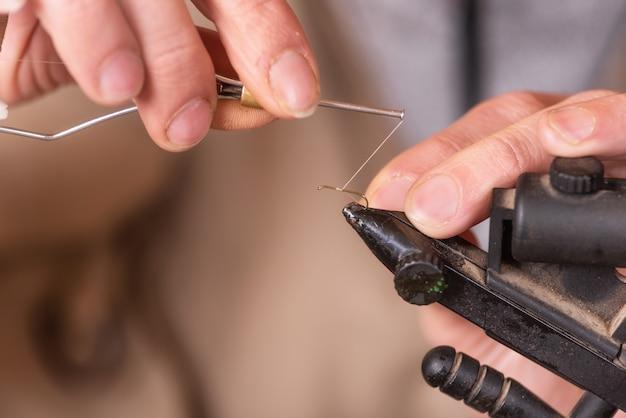 Chiuda in su del pescatore che lega una mosca per pescare.