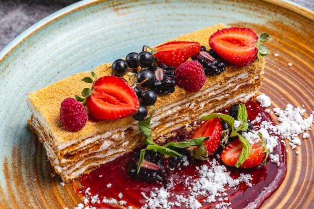 Chiuda in su del pezzo della torta di miele decorato con il ribes e la mora del lampone della fragola