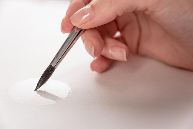 Chiuda in su del processo di disegno con la spazzola su libro bianco
