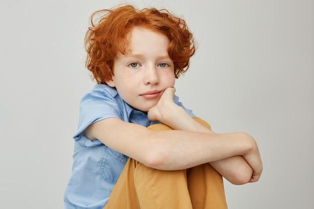 Chiuda in su del ragazzino divertente con capelli ondulati rossi che si siede sul pavimento, tenendo il viso con la mano