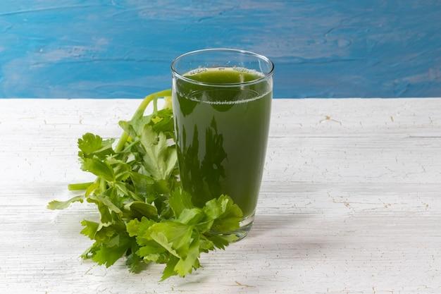 Chiuda in su del succo di sedano verde fresco su vetro