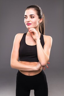 Chiuda in su del torso della donna adatta con le sue mani sulle anche sulla parete grigia