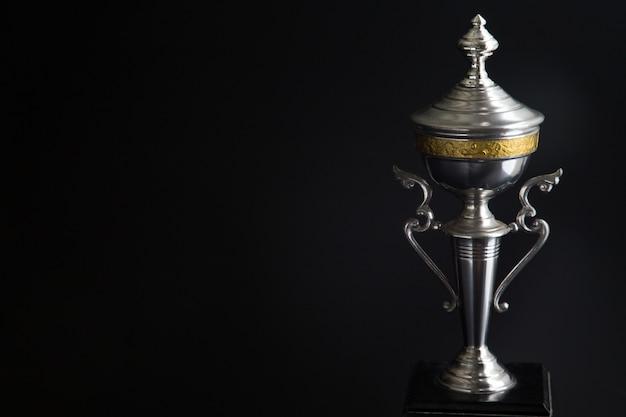Chiuda in su del trofeo d'argento sopra priorità bassa nera. premi vincenti
