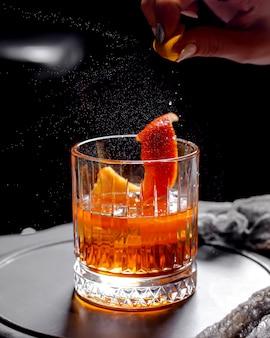 Chiuda in su del vetro di cristallo di viski con il cocktail dell'alcool guarnito con la scorza d'arancia