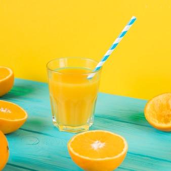 Chiuda in su del vetro fresco del succo d'arancia sulla tabella blu