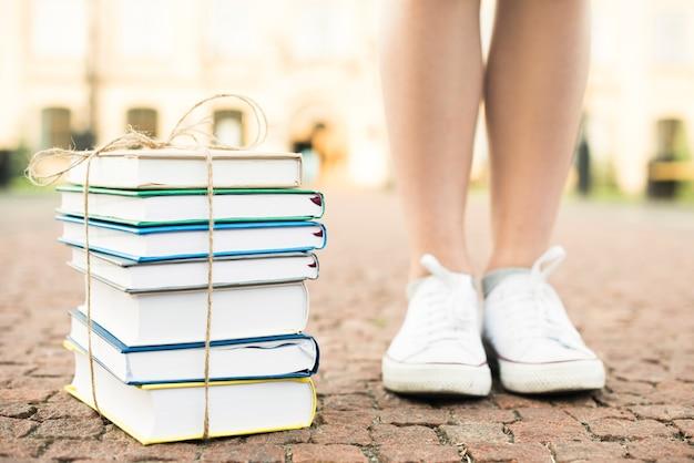 Chiuda in su dell'adolescente che si leva in piedi vicino ai libri
