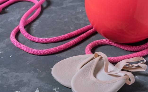 Chiuda in su dell'attrezzatura rythmic qymnastic. corda per saltare rosa, palla e scarpe per ginnastica su grigio