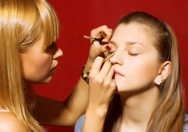Chiuda in su dell'estetista che crea il trucco per una giovane donna nel salone di bellezza.