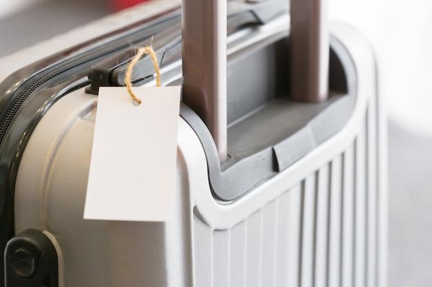 Chiuda in su dell'etichetta in bianco dell'etichetta dei bagagli su una valigia