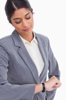 Chiuda in su dell'imprenditore femminile che esamina il suo orologio
