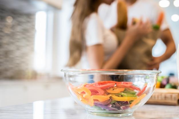 Chiuda in su dell'insalatiera sulla tabella con la priorità bassa confusa delle coppie nella cucina