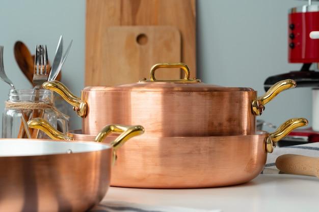 Chiuda in su dell'interiore moderno della cucina con pentole di rame