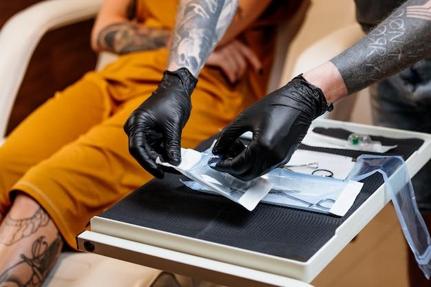Chiuda in su dell'uomo che apre l'attrezzatura sterile per il piercing.