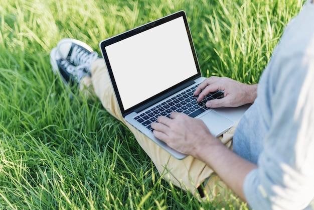 Chiuda in su dell'uomo che lavora con il computer portatile