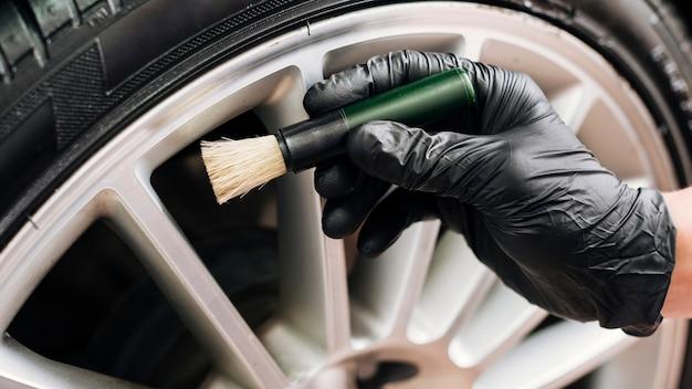 Chiuda in su dell'uomo che pulisce gli orli dell'automobile