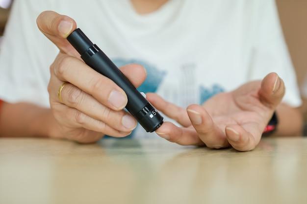 Chiuda in su dell'uomo che utilizza la lancetta sul dito per controllare il livello di zucchero nel sangue
