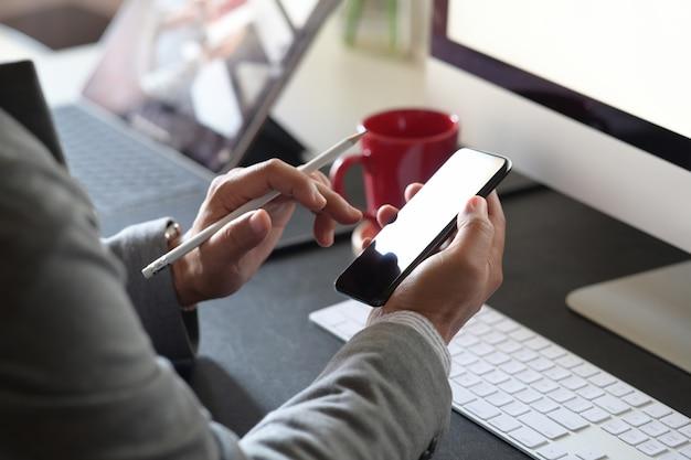 Chiuda in su dell'uomo con gli smartphones in ufficio