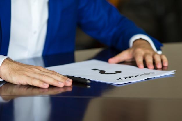 Chiuda in su dell'uomo d'affari che pensa su un documento del contratto