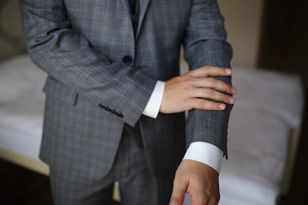 Chiuda in su dell'uomo d'affari in vestito sopra priorità bassa grigio scuro con lo spazio della copia