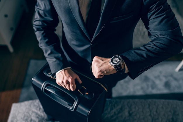 Chiuda in su dell'uomo d'affari serio in vestito che guarda l'orologio da polso e si prepara per il viaggio d'affari mentre si trovava in camera da letto.