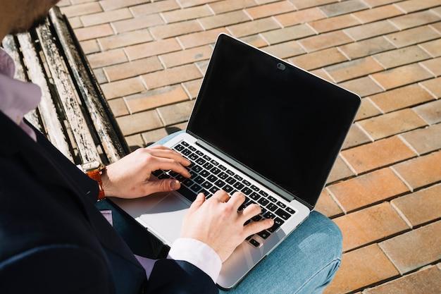 Chiuda in su dell'uomo d'affari usando il portatile all'aperto