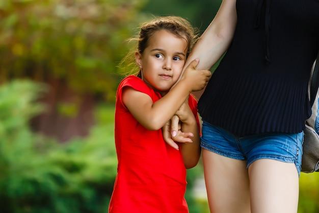 Chiuda in su della bambina infelice del bambino dalla pelle scura che piange mentre sua madre la tiene sulle mani.