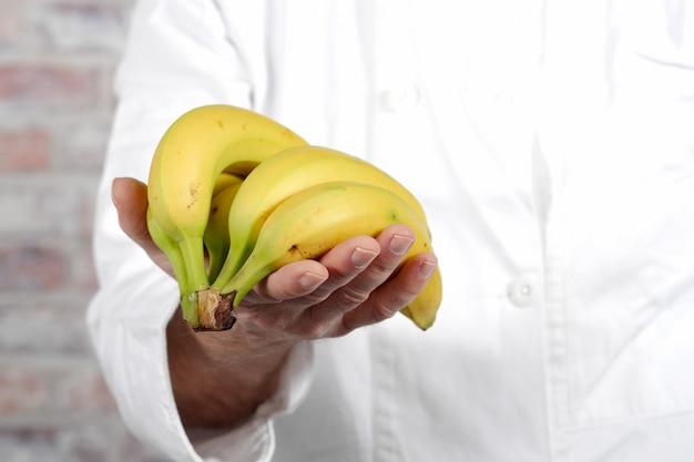 Chiuda in su della banana della holding dell'uomo della mano