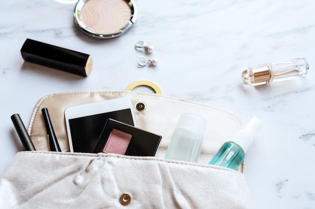 Chiuda in su della borsa della donna, degli accessori, del disinfettante e dello spruzzo dell'alcool. concetto di bellezza. deve avere l'oggetto nel concetto 2020. disteso