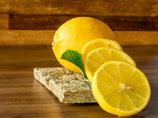 Chiuda in su della ciotola con i limoni e i fogli verdi su superficie di legno rustica
