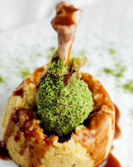 Chiuda in su della coscia di tacchino tempestata di granelli verdi disposti su purè di patate