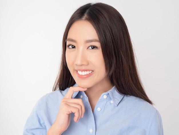 Chiuda in su della donna asiatica con i bei denti sulla parete bianca
