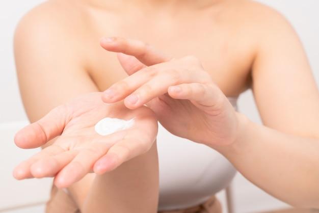 Chiuda in su della donna che applica la crema idratante