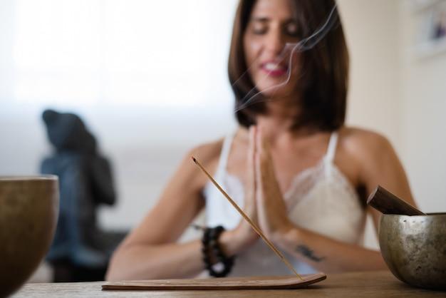 Chiuda in su della donna che brucia un bastoncino di incenso nel suo salotto. donna che medita in atmosfera buddista durante l'isolamento a casa.