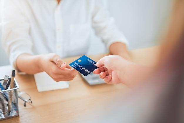Chiuda in su della donna che dà il pagamento con carta di credito dal cliente