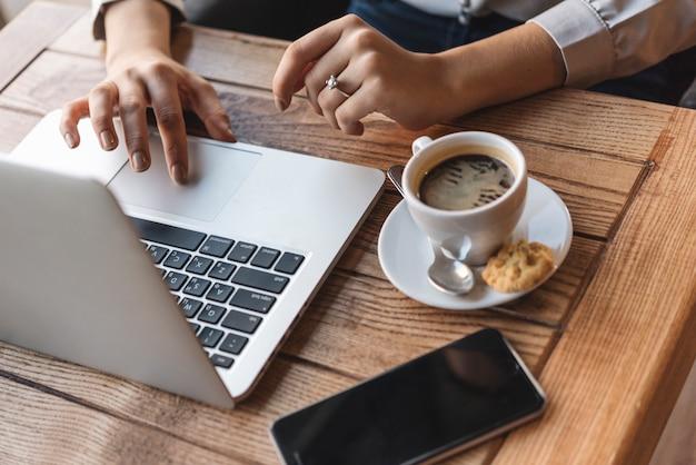 Chiuda in su della donna che digita sul computer portatile nella caffetteria