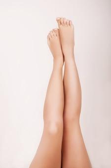 Chiuda in su della donna che fa il massaggio per le sue gambe lisce