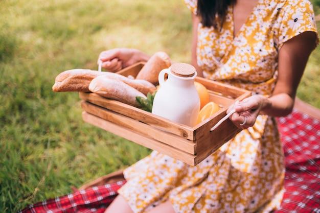Chiuda in su della donna che gode del picnic in un parco.
