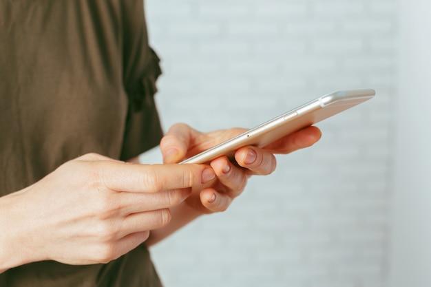 Chiuda in su della donna che manda un sms sullo smartphone