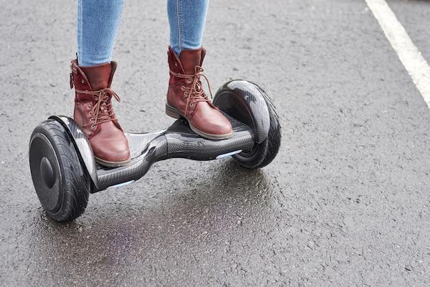 Chiuda in su della donna che usando il bordo di hover sulla strada asfaltata. piedi su scooter elettrico all'aperto
