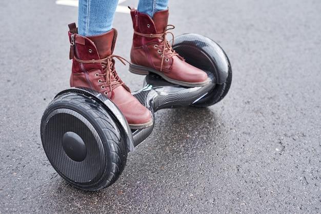 Chiuda in su della donna che usando il hoverboard sulla strada asfaltata. piedi su scooter elettrico all'aperto