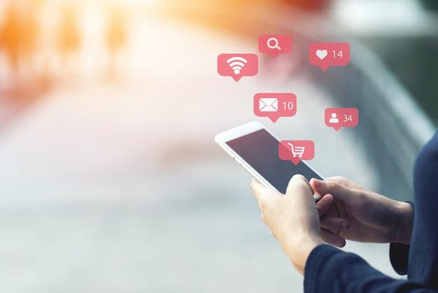 Chiuda in su della donna che usando il suo smartphone mobile all'aperto. shopping online concetto.
