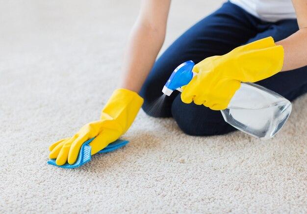 Chiuda in su della donna con il tappeto di pulizia del panno