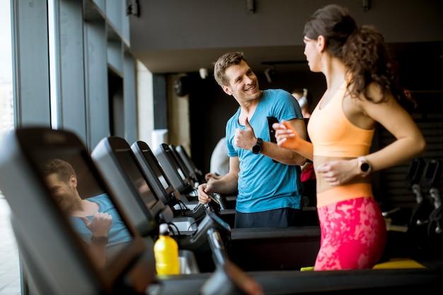 Chiuda in su della donna con l'addestratore che risolve sulla pedana mobile in ginnastica