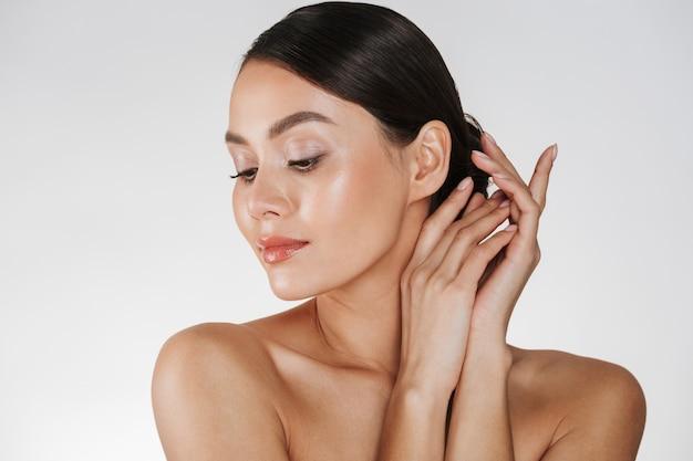 Chiuda in su della donna rilassata del brunette con pelle pulita che propone alla macchina fotografica con gli occhi chiusi, isolato sopra bianco