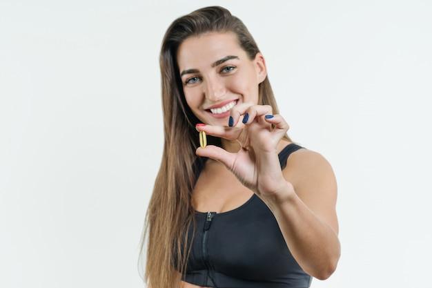 Chiuda in su della donna sorridente di forma fisica che cattura la pillola con olio di fegato di merluzzo