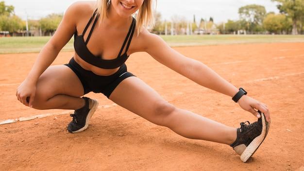 Chiuda in su della donna sportiva che si estende sulla pista dello stadio